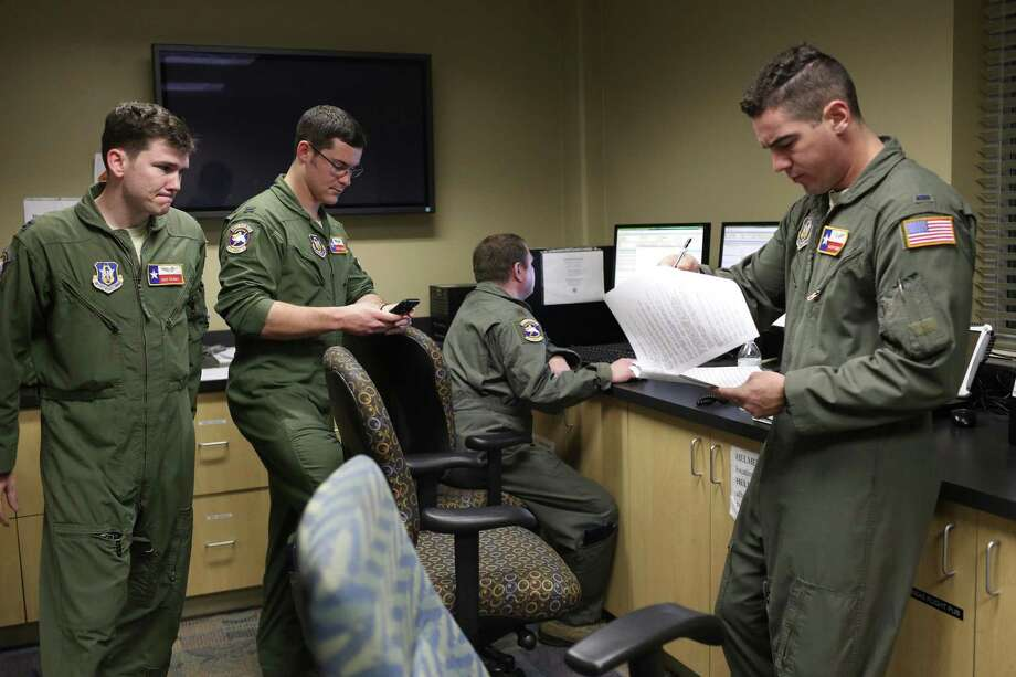 "From left standing, Capt. Mike Raggio, 1st. Lt. Richard ""Ross"" Quarre and 1st. Lt. David Fink go over the flight plan at Joint Base San Antonio-Lackland,  on Feb. 27. Sitting is Maj. Jeremy Hooper. They are members of the Air Force Reserve's 433rd Airlift Wing, known as the Alamo Wing. The crew was preparing for a flight to Fort Drum, New York to pick up U.S. Army UH-60 Blackhawk helicopters and soldiers from the U.S. Army 10th Combat Aviation Brigade, 10th Mountain Division. The cargo and troops were headed to Riga, Latvia in support of Operation Atlantic Resolve. Photo: JERRY LARA /San Antonio Express-News / © 2017 San Antonio Express-News"