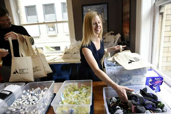 Meghan Freebeck, CEO and founder of Simply The Basics, right, and Bob Perry, board vice president, fill their company's tote bags with toiletries from bins at their office in San Francisco, CA, on Monday March 20, 2017.