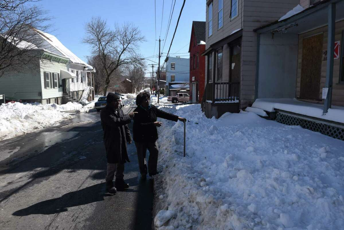Albany County legislator Luci McKnight, center, and her neighbor, Chuck Moore, left, stand next to a Third Ave. building across from McKnight?s home, far left, that was marked as vacant by the City of Albany on Friday, March 17, 2017, in Albany, N.Y. The markers are posted to help emergency personnel identify buildings that could present a safety risk if entered. Albany County legislator Luci McKnight, who lives on Third Ave., is concerned about the stigma they create. (Will Waldron/Times Union)