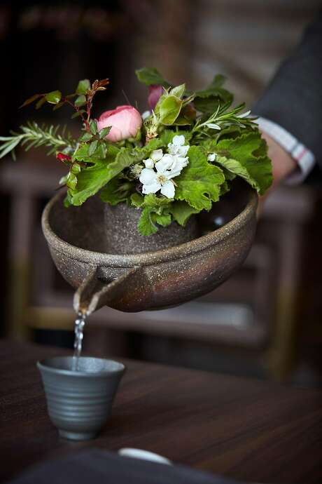 Sake is poured from a pitcher with a flower arrangement on top at Single Thread. Photo: John Lee, Special To The Chronicle