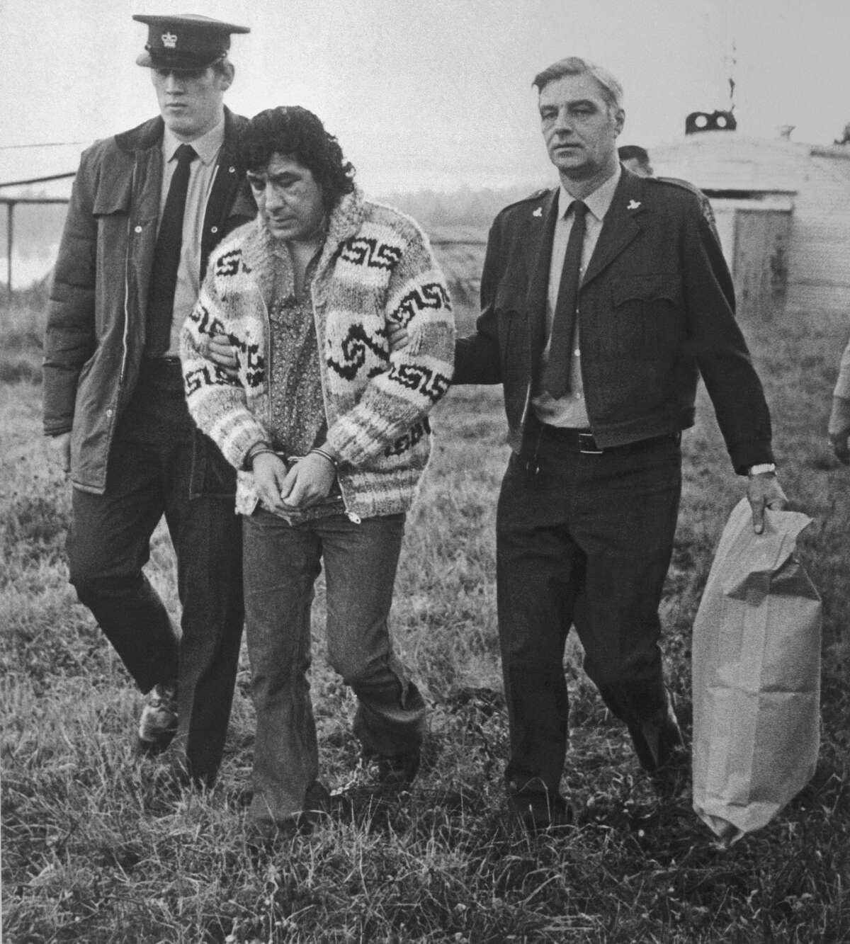 (Original Caption) Leonard Peltier, American Indian Movement leader, is led across Okalla prison exercise yard to a waiting helicopter. After a prolonged legal battle, Peltier was ordered deported by Canadian Justice Minister Ron Basford to face charges of murdering two FBI agents.