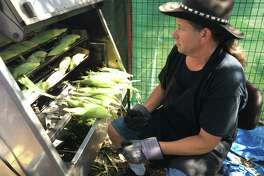 Longinos DeLeon places the uncooked corn into a machine that will roast it. Fields of Corn and its corn in a cup or corn on the cob has become a staple at the Houston Livestock Show and Rodeo.