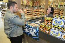 Andrew Dominick from Norwalk takes a taste of Ol'Factory Pils with Two Roads Brewing Co. Sales Manger Caitlin Guelakis  during a beer tasting at the opening day of the new LQR MKT liquor store on Thursday October 20, 2016 in Norwalk Conn.