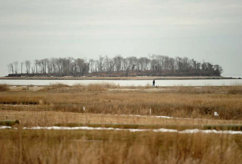 With Charles Island in the distance, a man walks the boardwalk at Silver Sands State Park in Milford, Conn. on Tuesday, March 21, 2017. A bill introduced by State Sen. Gayle Slossberg has passed in committee to halt the planned buildout  of the state park. The bill requires construction plans for the park to pass approval by the Milford Board of Aldermen. Photo: Brian A. Pounds / Hearst Connecticut Media / Connecticut Post