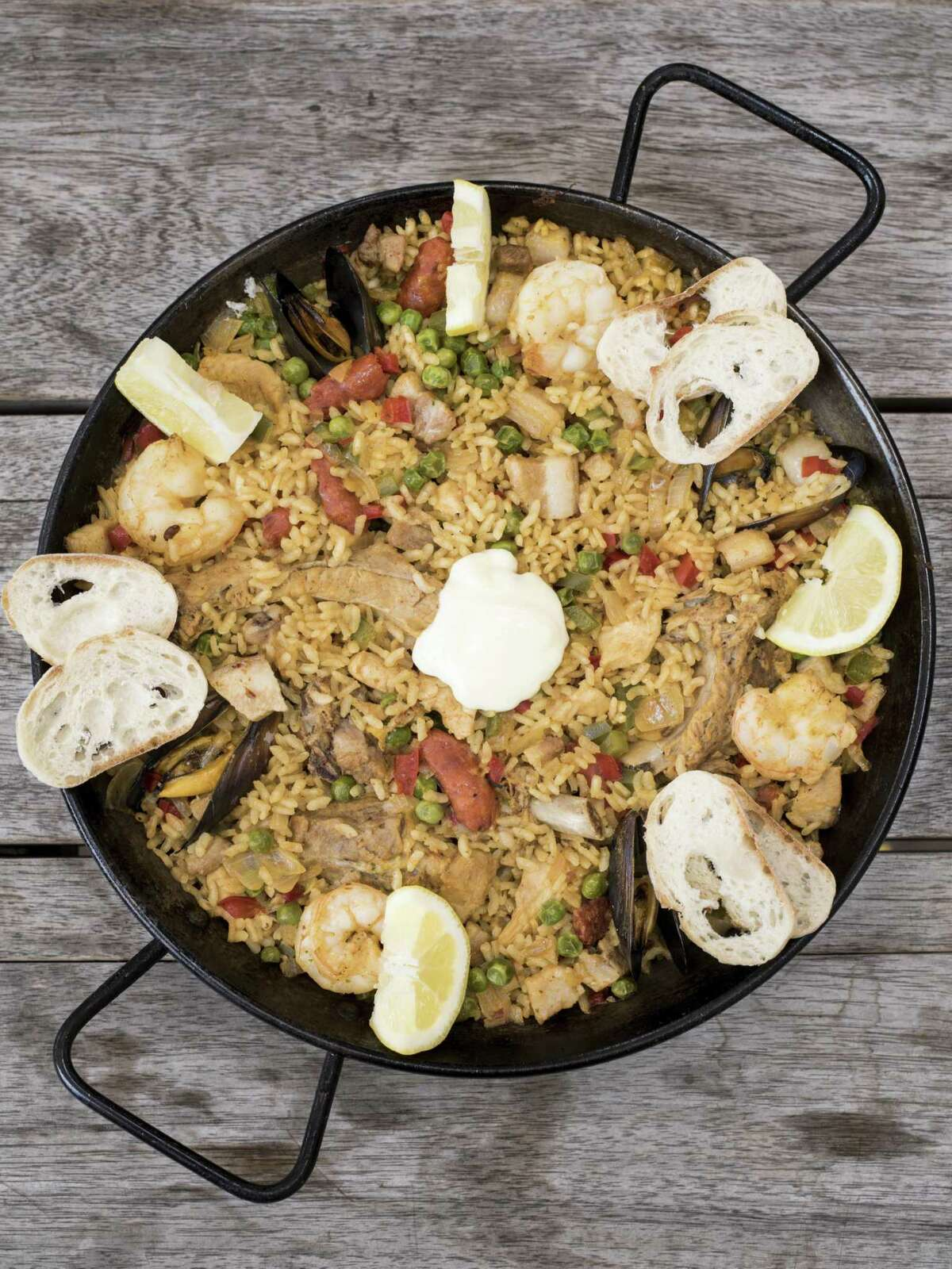 Toro Paella is made with pork belly chorizo, pork ribs, chicken, muscles, shrimp, rice, saffron water, parsley sauce, red and green peppers, onions, green peas and olive oil and cooked in a chicken and seafood broth at Toro Kitchen + Bar.