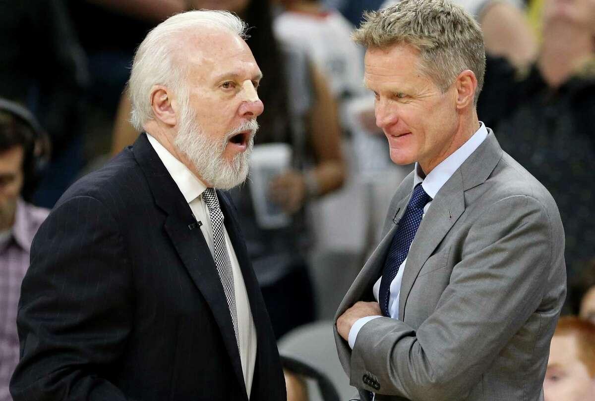 Spurs coach Gregg Popovich talks with Golden State Warriors coach Steve Kerr in 2017.