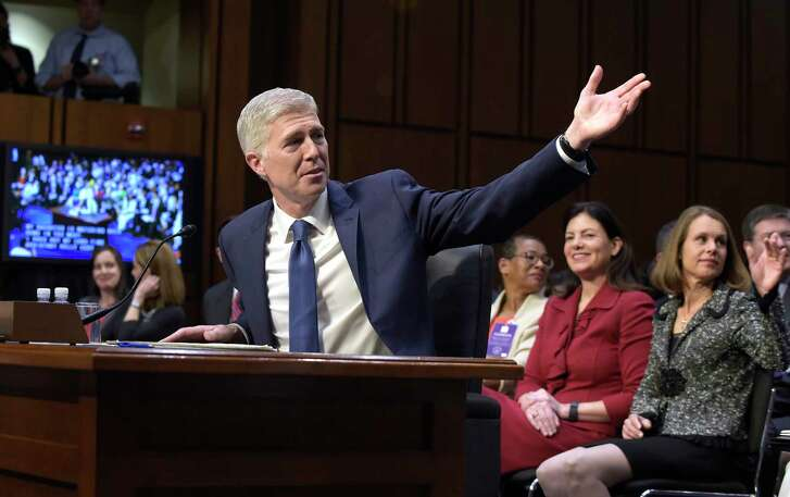 Supreme Court Justice nominee Neil Gorsuch recognized family members in the audience as he arrives on Capitol Hill in Washington, Monday, March 20, 2017, for his confirmation hearing before the Senate Judiciary Committee. His wife, Marie Louise Gorsuch, is at right. (AP Photo/Susan Walsh)