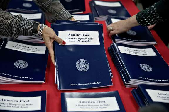 Employees arrange copies of U.S. President Donald Trump's fiscal 2018 budget request, America First: A Budget Blueprint to Make America Great Again, at the Government Printing Office (GPO) library in Washington, D.C., recently. His budget proposes defense spending increases and deep cuts in the arts, the EPA and the State Department.