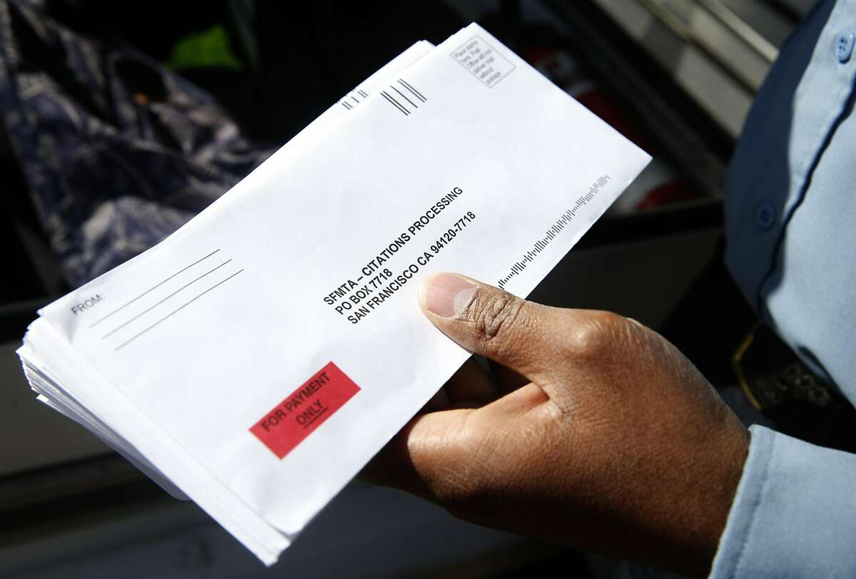 Trevor Adams, a parking control officer for the SFMTA, stocks up on envelopes before issuing parking tickets on Chestnut Street in the Marina District in San Francisco, Calif. on Tuesday, March 21, 2017.