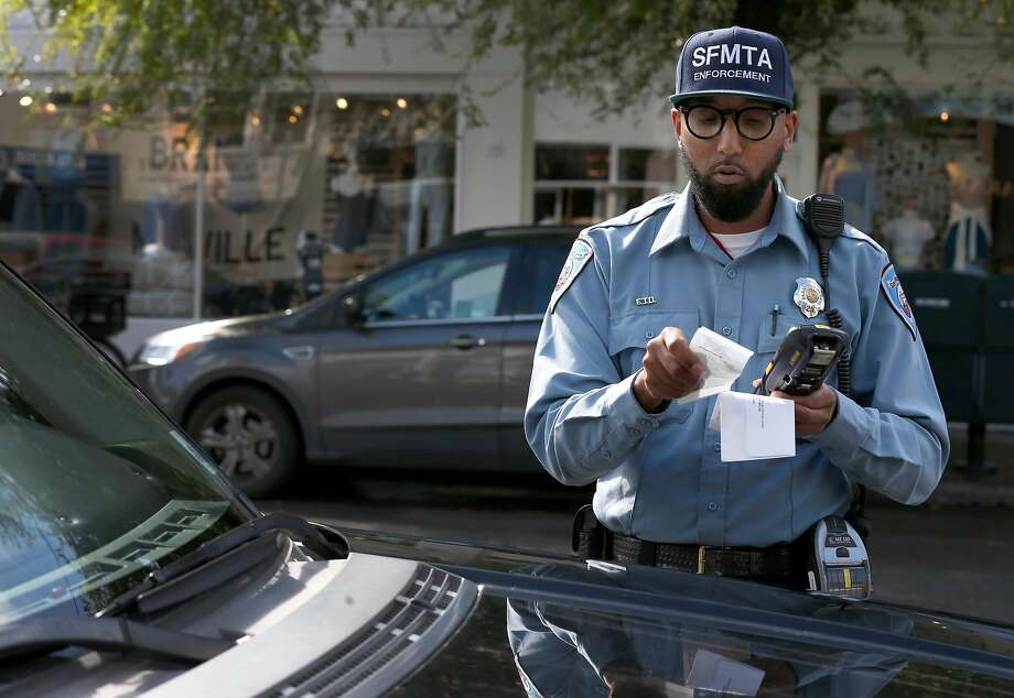 Trevor Adams, a parking control officer for the SFMTA, prints a parking ticket to a car parked at an expired meter on Chestnut Street in the Marina District in San Francisco, Calif. on Tuesday, March 21, 2017. Photo: Paul Chinn, The Chronicle