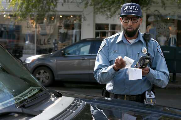 Trevor Adams, a parking control officer for the SFMTA, prints a parking ticket to a car parked at an expired meter on Chestnut Street in the Marina District in San Francisco, Calif. on Tuesday, March 21, 2017.