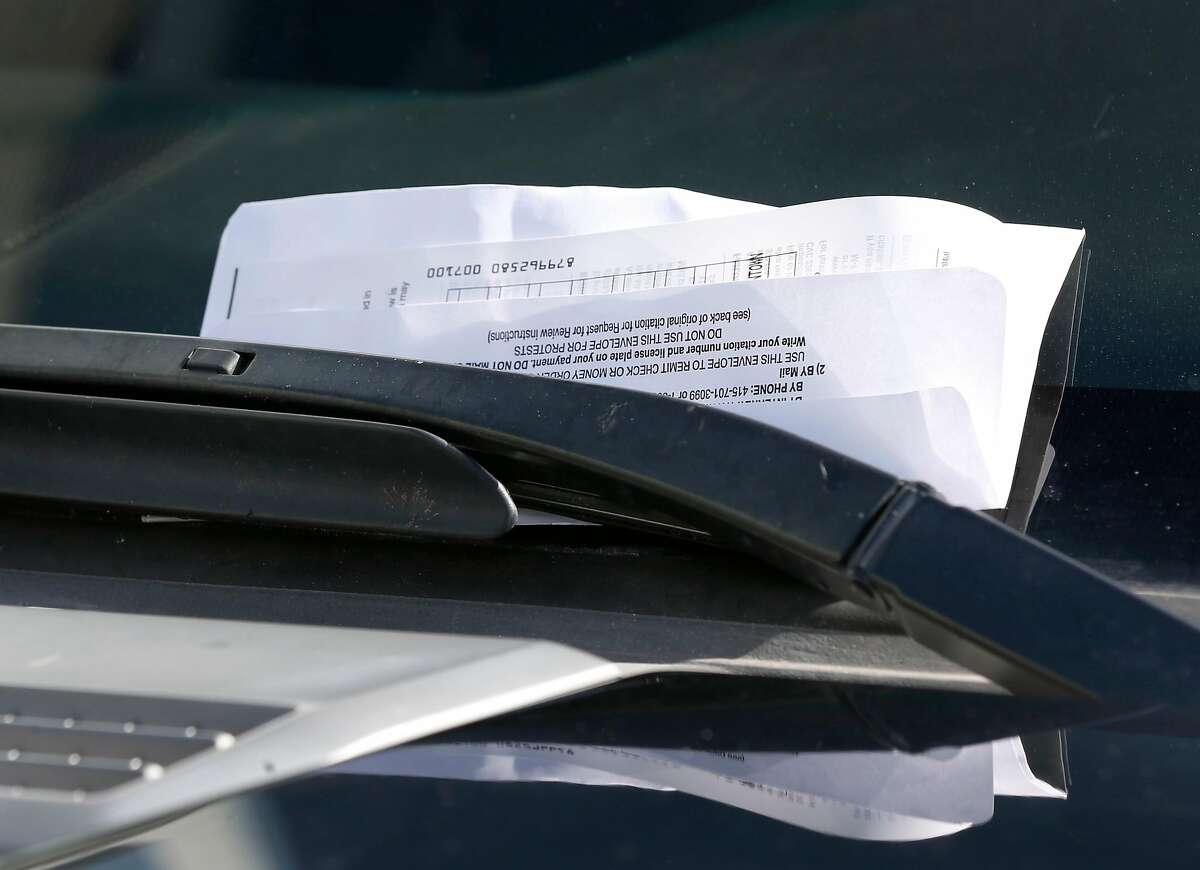 A parking ticket issued by SFMTA parking control officer Trevor Adams is attached to a car windshield on Chestnut Street in the Marina District in San Francisco, Calif. on Tuesday, March 21, 2017.