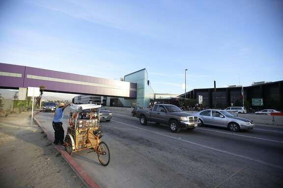 The Cross Border XPress pedestrian bridge between San Diego and the Tijuana Airport on December 8, 2015, with a street vendor outside the Tijuana, Mexico, airport. (Alejandro Tamayo/San Diego Union-Tribune/TNS)