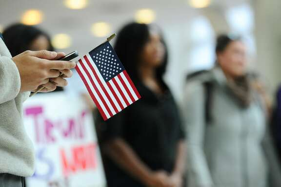 A student looks at a photo he took while holding an American flag during the anti-Trump, anti-system demonstration inside UConn Stamford in Stamford, Conn. on Thursday, Nov. 10, 2016.