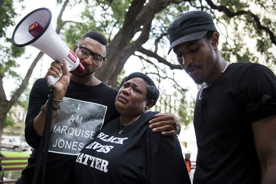 Deborah Bush, aunt of Marquise Jones who was killed by police, cries while Mike Lowe, left, and Johnathan-David Jones speak during a rally put on by the Black Lives Matter movement before the City Council meeting on August 31, 2016 in San Antonio, Texas.  Councilman Rey Salda–a and some community members are fighting to kill a proposed collective-bargaining agreement for the San Antonio Police Officers Association because they say it doesnÕt do enough to reform disciplinary procedures for officers or add transparency and accountability. The council is set to vote Thursday on the contract. Photo: Carolyn Van Houten / Carolyn Van Houten / 2016 San Antonio Express-News