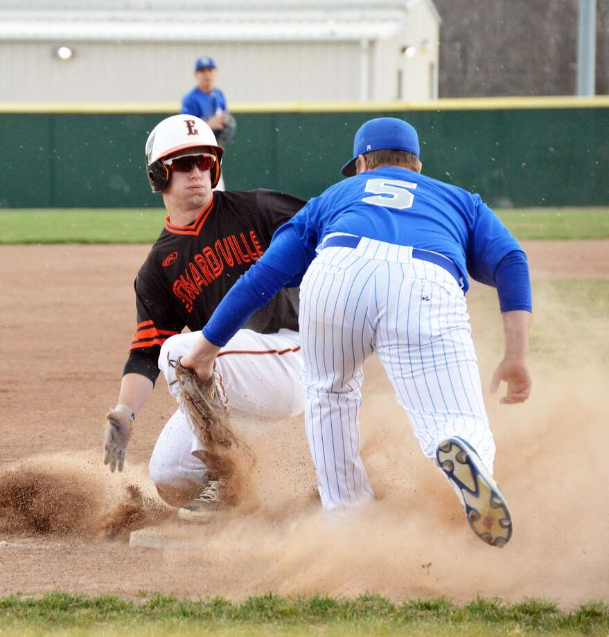 Edwardsville's Dylan Burris, left, slides safely into third base for a stolen base in the first inning against Greenville.