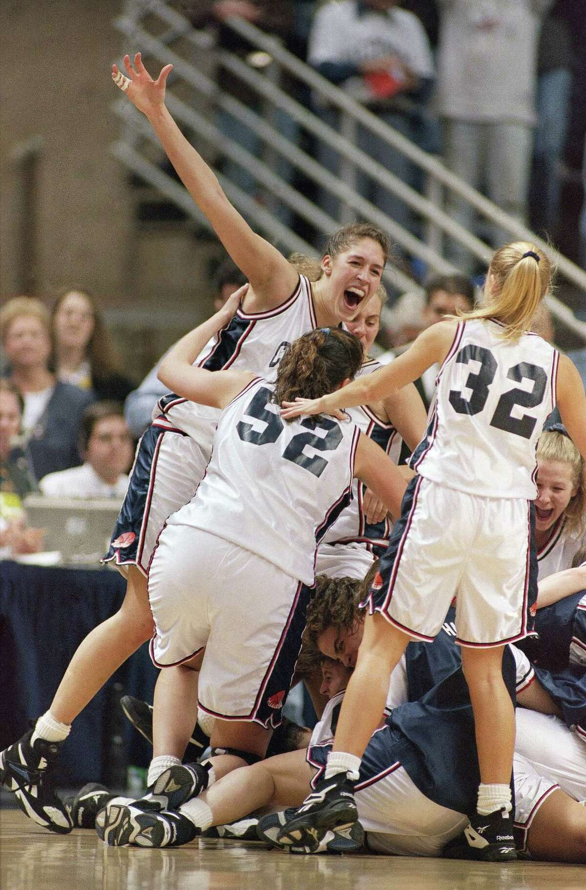 FILE - In this April 3, 1995, file photo, UConn's Rebecca Lobo, left, celebrates with teammates including Kara Wolters (52) and Pam Weber (32) after they defeated Virginia 67-63 to win the NCAA East Regional Championship, in Storrs, Conn. No current UConn player was even born the last time this program had a losing streak. And that mark is safe for at least another year, which has Rebecca Lobo thinking about popping the champagne with her former teammates _ the ones who actually lost two in a row. (AP Photo/John Dunn, File) ORG XMIT: NY166