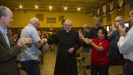 Father Christopher Phillips is greeted with a standing ovation by parishioners at Our Lady of Atonement Catholic Church, Tuesday, March 21, 2017.
