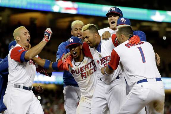 Puerto Rico team members celebrate their win over the Netherlands in a semifinal in the World Baseball Classic in Los Angeles, Monday, March 20, 2017. (AP Photo/Chris Carlson)