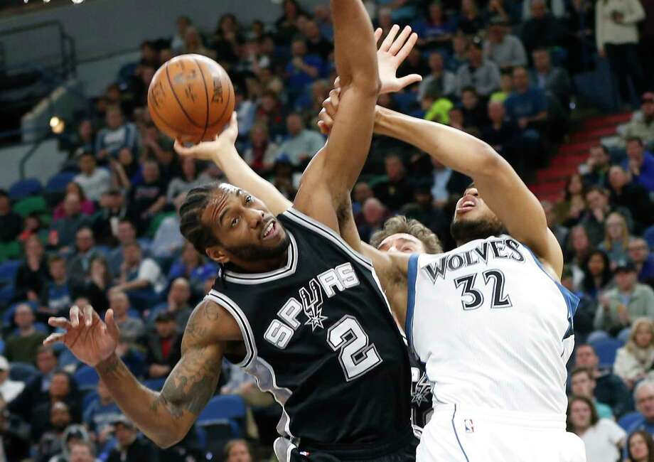 Minnesota Timberwolves' Karl-Anthony Towns, right, gets tangled up with San Antonio Spurs' Kawhi Leonard during the second half of an NBA basketball game Tuesday, March 21, 2017, in Minneapolis. The Spurs won 100-93. (AP Photo/Jim Mone) Photo: Jim Mone, Associated Press / Copyright 2017 The Associated Press. All rights reserved.