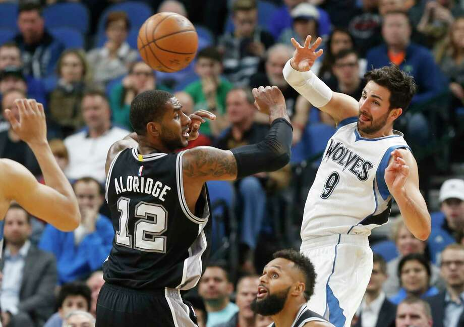 Minnesota Timberwolves' Ricky Rubio, right, of Spain, sends a pass over San Antonio Spurs' LaMarcus Aldridge during the first half of an NBA basketball game Tuesday, March 21, 2017, in Minneapolis. (AP Photo/Jim Mone) Photo: Jim Mone, Associated Press / Copyright 2017 The Associated Press. All rights reserved.