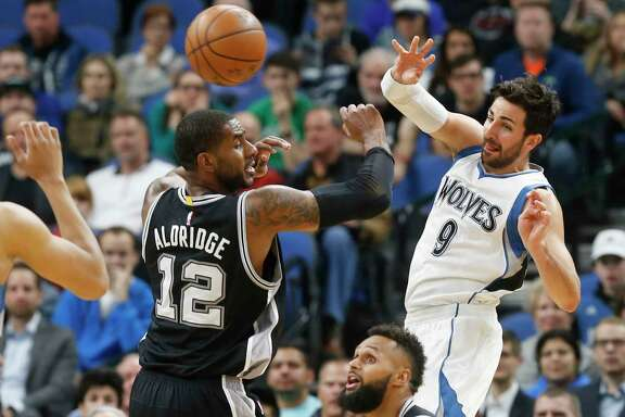 Minnesota Timberwolves' Ricky Rubio, right, of Spain, sends a pass over San Antonio Spurs' LaMarcus Aldridge during the first half of an NBA basketball game Tuesday, March 21, 2017, in Minneapolis. (AP Photo/Jim Mone)