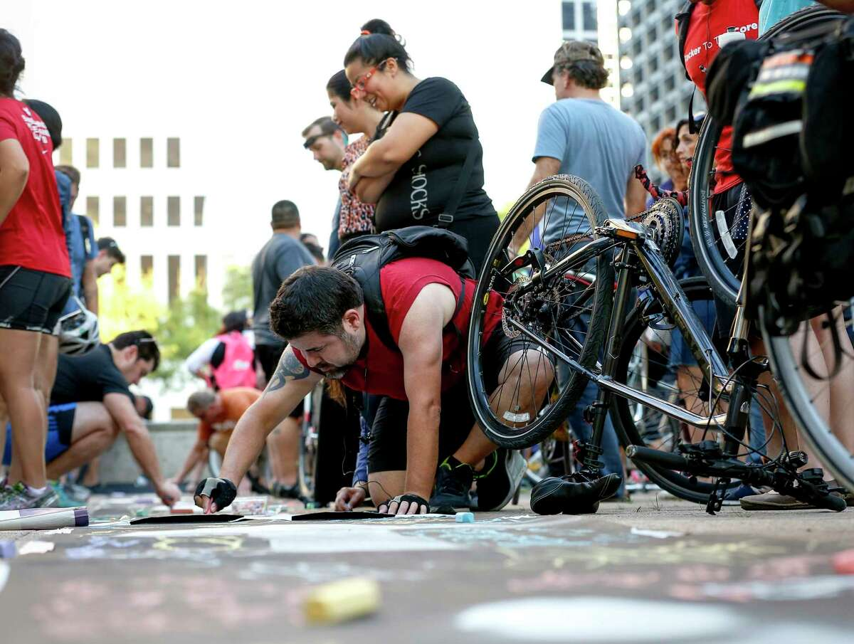 Anthony Alaniz, center in red, adds his name to a symbolic bike lane during a rally for the Houston Bike Plan at Houston City Hall on March 21.
