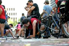 Anthony Alaniz, center in red, adds his name to a symbolic bike lane during a rally for the Houston Bike Plan at City Hall, Tuesday, March 21, 2017, in Houston.