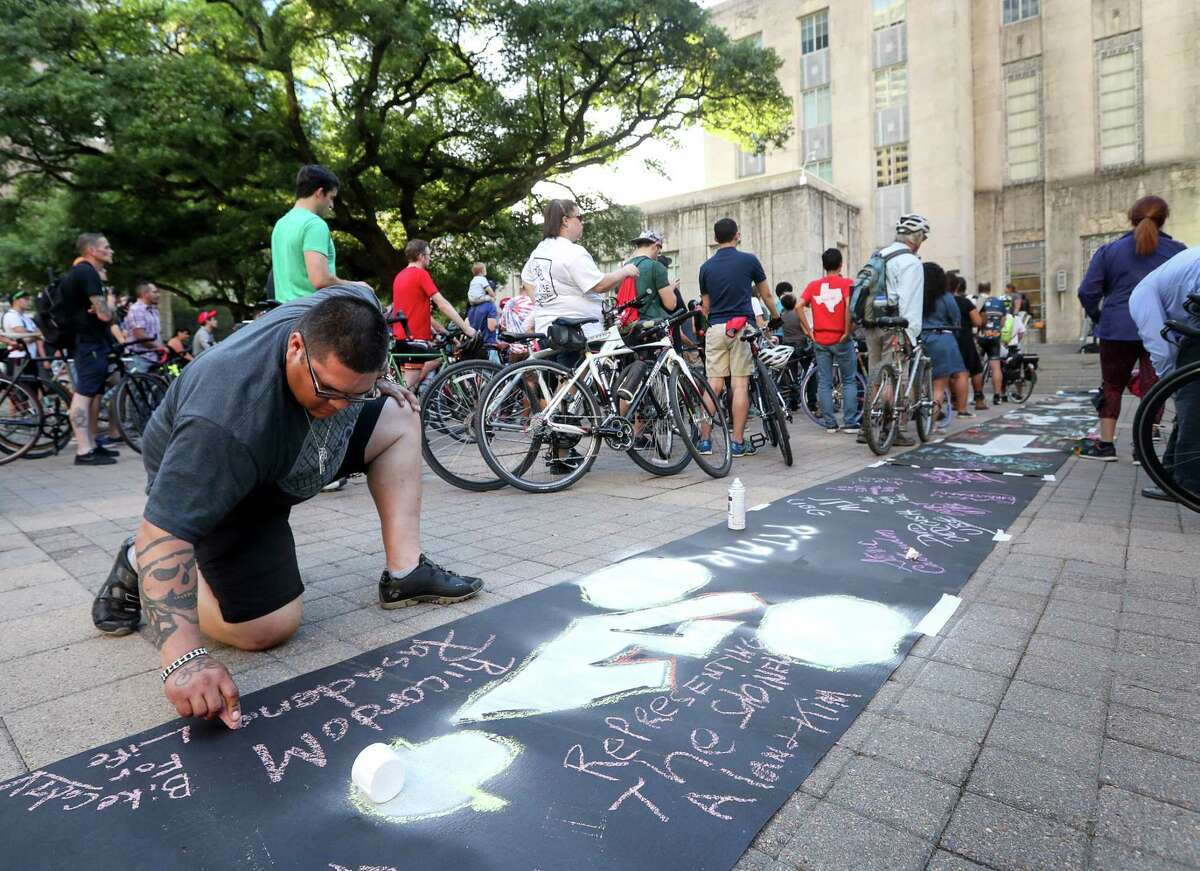 Ricardo Martinez, left, from Pasadena, adds his name to a symbolic bike lane during a rally for the Houston Bike Plan at City Hall, Tuesday, March 21, 2017, in Houston.