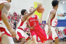 ERIN KIRKLAND | ekirkland@mdn.net  Beecher's Jordan Roland tries to block Beaverton's Carter Johnston on Tuesday at Bay City Central High School. The Buccaneers beat the Beavers 66-32 in the boys' basketball Class C quarterfinal game.