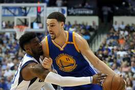 Dallas Mavericks guard Wesley Matthews (23) reaches in to steal the ball away from Golden State Warriors' Klay Thompson (11) in the first half of an NBA basketball game Tuesday, March 21, 2017, in Dallas. (AP Photo/Tony Gutierrez)