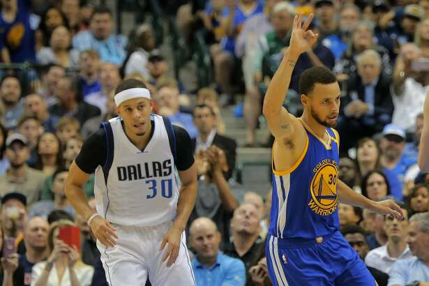 The Golden State Warriors' Stephen Curry, right, signals to his team after a score as he and his brother, the Dallas Mavericks' Seth Curry, left, come down court at American Airlines Center in Dallas on Tuesday, March 21, 2017. (Rodger Mallison/Fort Worth Star-Telegram/TNS)