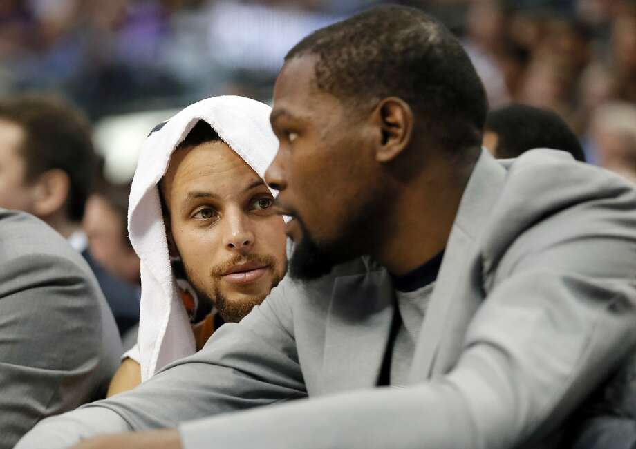 Golden State Warriors guard Stephen Curry, left, talks with Kevin Durant, right, in the first half of an NBA basketball game against the Dallas Mavericks on Tuesday, March 21, 2017, in Dallas. (AP Photo/Tony Gutierrez) Photo: Tony Gutierrez, Associated Press