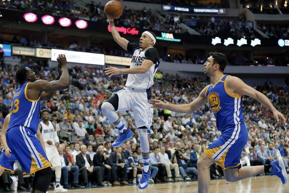 Golden State Warriors forward Draymond Green (23) and Zaza Pachulia, right, defend as Dallas Mavericks guard Seth Curry (30) goes up for a shot in the second half of an NBA basketball game, Tuesday, March 21, 2017, in Dallas. (AP Photo/Tony Gutierrez)