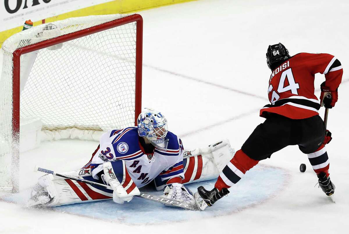 New Jersey Devils left wing Joseph Blandisi (64) makes a move on New York Rangers goalie Antti Raanta (32), of Finland, to score the game winning goal during the overtime of an NHL hockey game, Tuesday, March 21, 2017, in Newark, N.J. The Devils won 3-2. (AP Photo/Julio Cortez) ORG XMIT: NJJC113