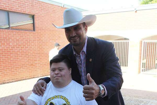Webb County Judge Tano Tijerina poses for a picture with a local in celebration of World Down Syndrome Day on Tuesday.