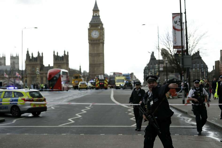 """Police secure the area on the south side of Westminster Bridge close to the Houses of Parliament in London, Wednesday, March 22, 2017. The leader of Britain's House of Commons says a man has been shot by police at Parliament. David Liddington also said there were """"reports of further violent incidents in the vicinity."""" London's police said officers had been called to a firearms incident on Westminster Bridge, near the parliament. Britain's MI5 says it is too early to say if the incident is terror-related. (AP Photo/Matt Dunham)"""