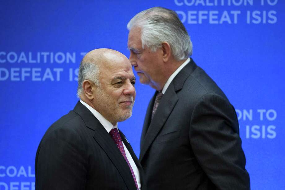 Secretary of State Rex Tillerson, right, passes behind Iraqi Prime Minister Haider al-Abadi as he walks to the podium to speak at the Meeting of the Ministers of the Global Coalition on the Defeat of ISIS, Wednesday, March 22, 2017, at the State Department in Washington. Top officials from the 68-nation coalition fighting the Islamic State group are looking to increase pressure on the group as U.S.-backed forces move closer to retaking Mosul. (AP Photo/Cliff Owen) Photo: Cliff Owen, FRE / Associated Press / FR170079 AP