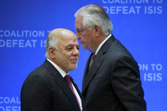 Secretary of State Rex Tillerson, right, passes behind Iraqi Prime Minister Haider al-Abadi as he walks to the podium to speak at the Meeting of the Ministers of the Global Coalition on the Defeat of ISIS, Wednesday, March 22, 2017, at the State Department in Washington. Top officials from the 68-nation coalition fighting the Islamic State group are looking to increase pressure on the group as U.S.-backed forces move closer to retaking Mosul. (AP Photo/Cliff Owen)