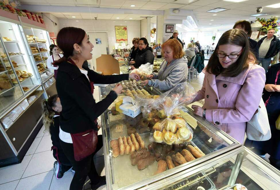 Katie Johnson, left assists a customer as business was extremely heavy the day before the Thanksgiving holiday Wednesday morning Nov. 25, 2015 at the Bella Napoli Bakery in Latham, N.Y. (Skip Dickstein/Times Union)