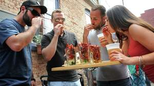 From left, Nick Bloomingdale of Clifton Park, Tyler Mason of Malta, Vincent Barber of Stillwater and Teresa Mason of Malta enjoy their orders of crawdaddies during a crawfish festival at Hattie's on Monday, May 25, 2015 in Saratoga Springs, N.Y. (Lori Van Buren / Times Union)
