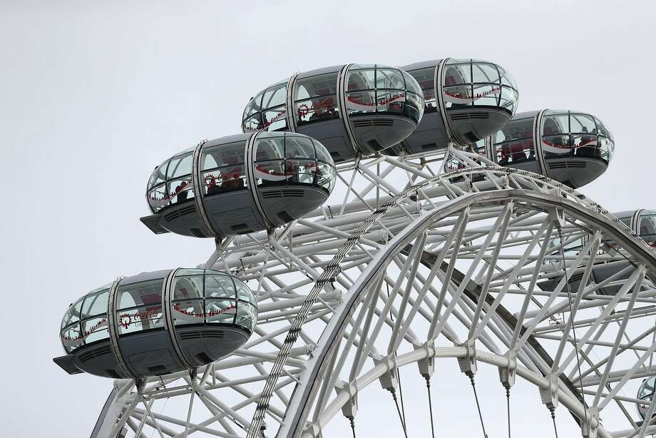 """People remain in pods on the London Eye after it was stopped, after a policeman was stabbed and his apparent attacker shot by officers in a major security incident near to the Houses of Parliament in London, Wednesday March 22, 2017.  In a separate incident a car drove into a pedestrian on nearby Westminster Bridge.  Authorities said they were treating the attack as a """"terrorist incident until we know otherwise."""" (Jonathan Brady/PA via AP) Photo: Jonathan Brady, Associated Press"""