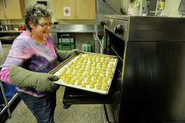 Sue Kimball from Clifton Park, and a member of the Congregation Gates of Heaven, pulls out a tray of knishes from the oven on Sunday, March 15, 2015, in Schenectady, N.Y.  Members of the synagogue are working to prepare food for their 12th annual Jewish Food Festival which will be held on Sunday, March 22nd from noon to 3:00pm.  Peter Kopcha, chair of the festival, said that the event gives the synagogue members a chance to share their Jewish culture with guests and the community at large through food.  (Paul Buckowski / Times Union)