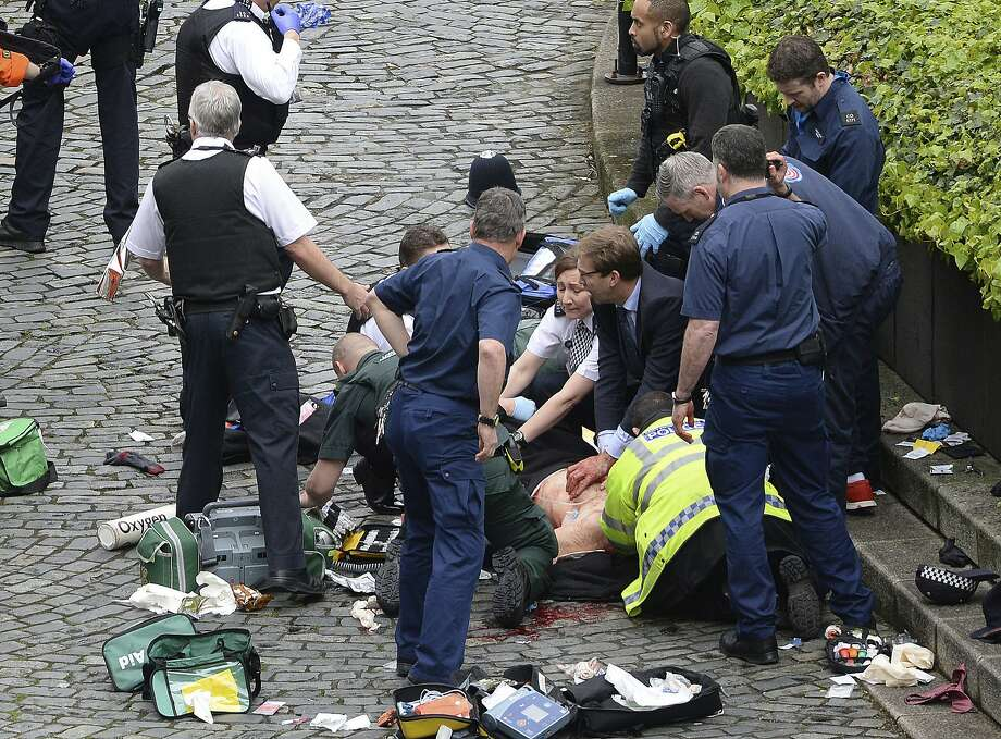 Conservative Member of Parliament Tobias Ellwood (center) performed first aid on a wounded police officer, who later died. Photo: Stefan Rousseau, Associated Press