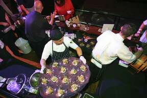 18 Oaks restaurant workers arrange Texas Wagyu beef carpaccio at the Express-News Top 100 Dining & Drinks launch party at the Aztec Theatre.