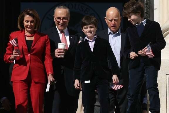 WASHINGTON, DC - MARCH 22:  U. S. House Minority Leader Rep. Nancy Pelosi (D-CA) (L), Senate Minority Leader Sen. Charles Schumer (D-NY) (2nd L), California Governor Jerry Brown (4th L), and Pelosi's grandsons Paul Vos (R) and Thomas Vos (3rd L) walk down the steps for an event on health care at the House East Front of the Capitol March 22, 2017 in Washington, DC. House Democrats held the event to mark the seventh anniversary of the Affordable Care Act.  (Photo by Alex Wong/Getty Images)