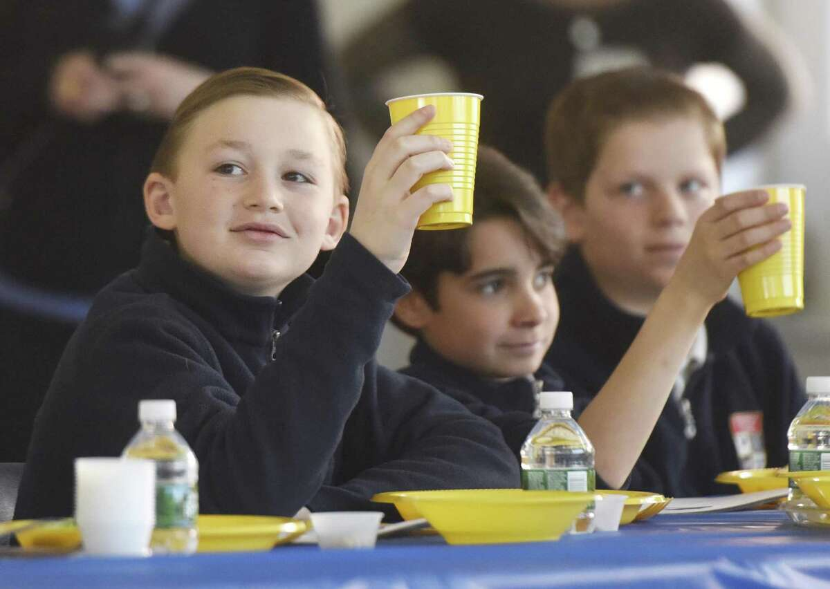 GCS fifth-grader Christian Sorbera, left, raises a glass during the Passover Seder at Greenwich Catholic School in Greenwich, Conn. Wednesday, March 22, 2017. As an annual traditional, Temple Sholom Rabbi Mitchell M. Hurvitz led GCS fifth-graders through a traditional Passover meal to highlight the similarities between Judaism and Catholicism, and and stress acceptance of all religions.