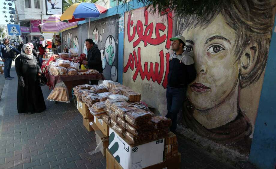 A Palestinian street vendor displays his goods in front of a mural painting in Gaza City on on March 8, 2017. (Photo by Majdi Fathi/NurPhoto via Getty Images) Photo: NurPhoto / NurPhoto Via Getty Images / Majdi Fathi/NurPhoto