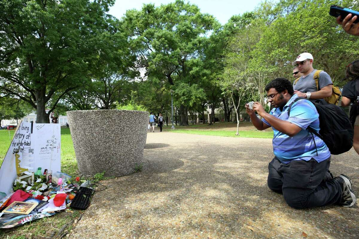 University of Houston student Cam Morris takes a picture of the memorial for Alex, a white-tailed squirrel known to students for being a good luck charm before tests Wednesday, March 22, 2017, in Houston.