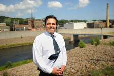 Ansonia Mayor David Cassetti stands across the Naugatuck River from the former Ansonia Copper & Brass property in Ansonia, Conn. on Monday, July 28, 2014. The property is one of many in the city that the mayor hopes to sell for redevelopment.